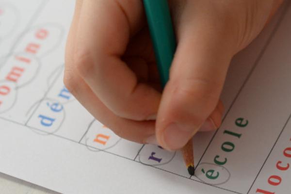 Un enfant entoure les syllabes du mot école